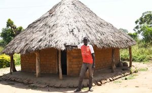 20-year-old Isaac Ewicu stands outside his newly constructed house in Bugondo village, in Serere District, Eastern Region, Uganda. Photo: Mavis Eleano/ICRISAT.