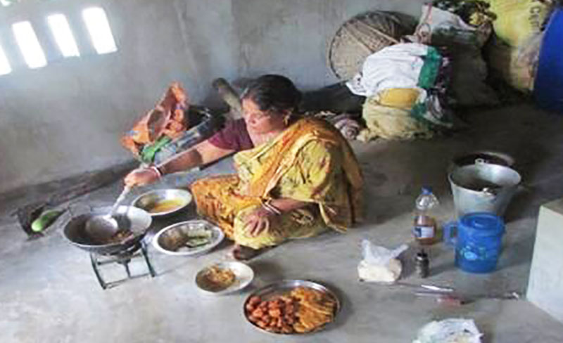 A woman in Sundarbon - India making snacks using flour from her new grass pea harvest to sell in local market.